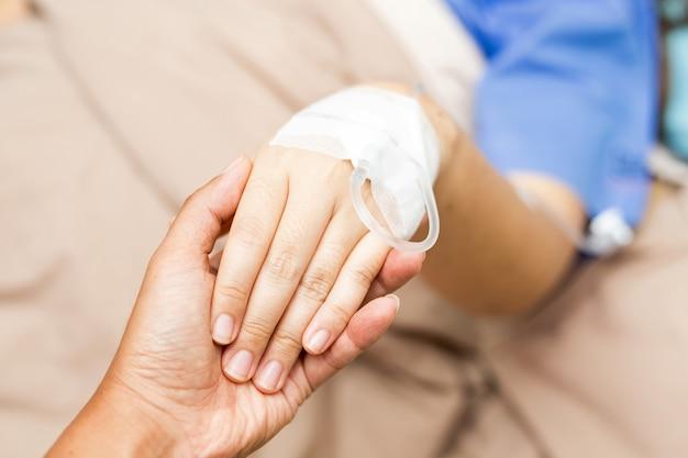 Marido que sostiene su mano paciente mujer de asia en la habitación del paciente