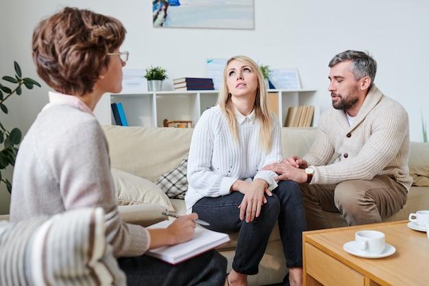 Marido tratando de llevarse bien con la esposa en la sesión de terapia