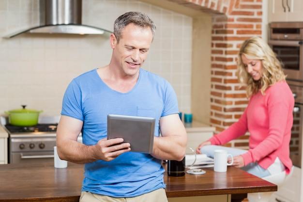 Marido usando tableta mientras esposa desayunando en la cocina