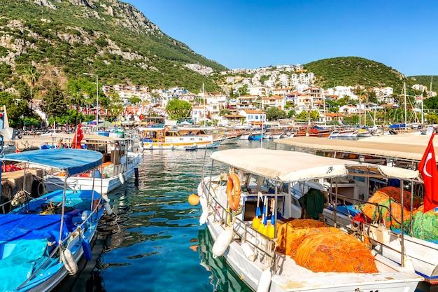 Marina con barcos de pesca y yates en una ciudad turística soleada.