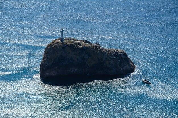 Marina. rock island con una cruz en la parte superior. un barco de recreo sobre un fondo de roca. paseos en barco y aventuras.