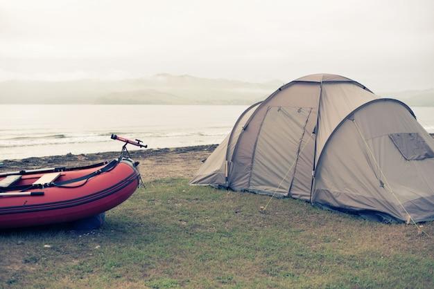 Marina de verano máquina de viaje tienda de campaña barco de goma costa horizonte horizonte cielo con nubes