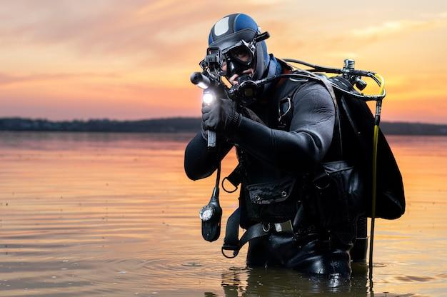 El marine sale del agua y se mueve hacia el objetivo con las armas en la mano. el concepto de videojuegos, publicidad, inestabilidad en el mundo, conflictos entre países. técnica mixta