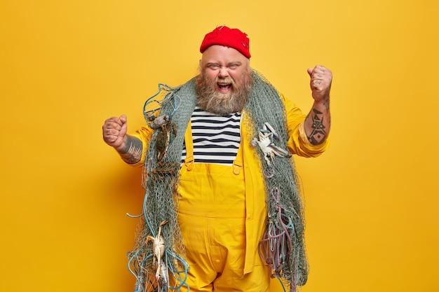 Marinero masculino emocional molesto o marinero profesional tiene poses de crucero por el mar con una red de pesca, levanta brazos tatuados y grita indignado, usa sombrero rojo y monos amarillos en el interior. concepto de vida marina