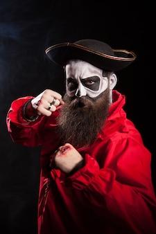 Marinero medieval con barba y sombrero aislado sobre fondo negro. disfraz de halloween.
