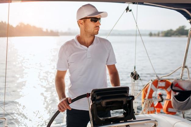 El marinero profesional se para al timón del yate y lo sostiene con las manos.