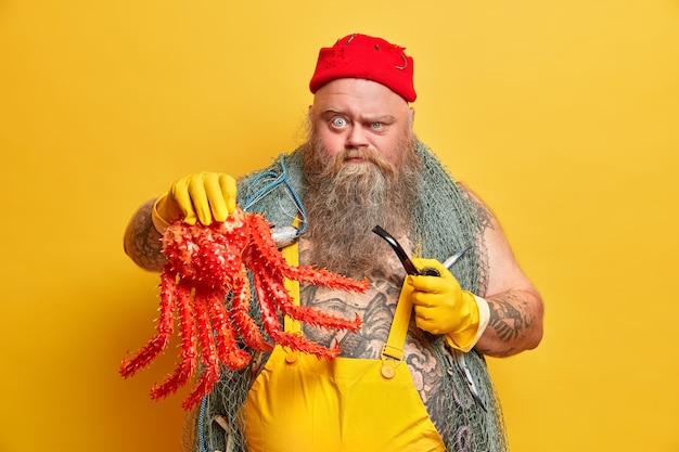Marinero serio y regordete tiene buen conocimiento de las reglas del mar, habilidades de pesca, muestra un gran pulpo rojo, fuma pipa, listo para recibir órdenes de los superiores