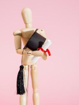 Marioneta de madera con un pequeño gorro de graduación y diploma