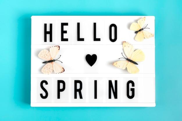 Mariposa, caja de luz con cita hola primavera sobre fondo azul endecha plana