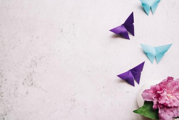 Mariposa de papel origami azul y púrpura con florero