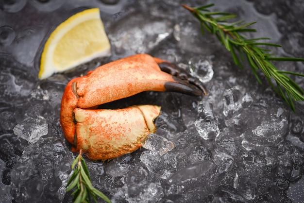 Mariscos congelados garras de cangrejo hervido / cangrejo fresco con ingredientes limón romero sobre hielo en el mercado