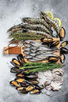 Mariscos crudos langostinos tigre, gambas, mejillones azules, pulpos, sardinas, olía. superficie blanca. vista superior.