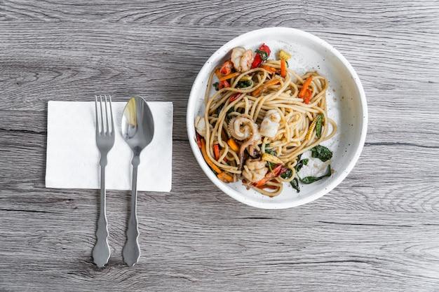Mariscos espaguetis fritos con salsa de tomate pimienta negra en plato blanco.
