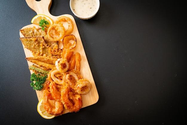 Mariscos fritos (camarones y calamares) con una mezcla de vegetales - estilo de comida poco saludable