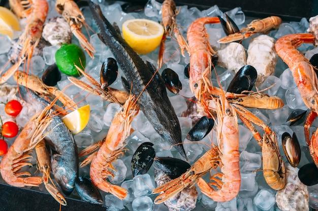 Mariscos en hielo. cangrejos, esturiones, mariscos, camarones, rapana, dorado, sobre hielo blanco.