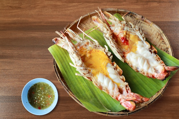 Mariscos tailandeses camarones río quemado con salsa picante en mesa de madera