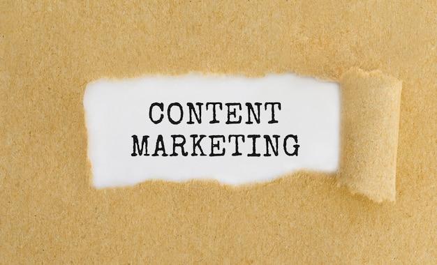 Marketing de contenido de texto que aparece detrás de papel marrón rasgado