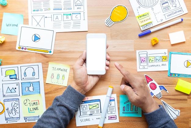 Marketing digital empresarial con boceto de papeleo y mano masculina tocando el teléfono inteligente