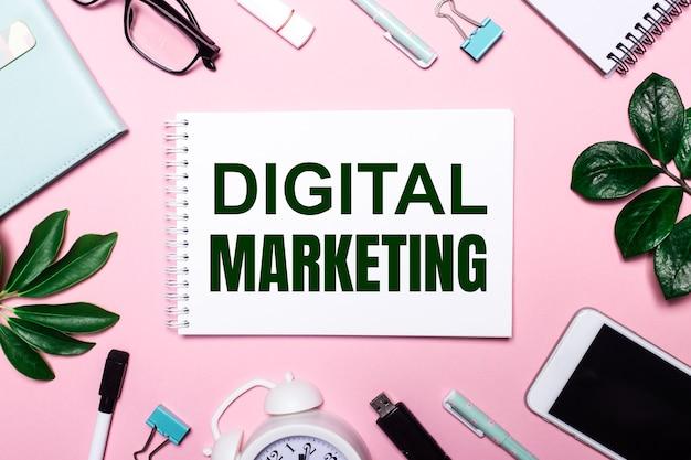 Marketing digital está escrito en un cuaderno blanco sobre una superficie rosa rodeada de accesorios comerciales y hojas verdes