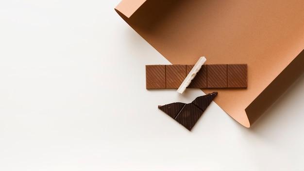 Marrón; barra de chocolate blanco y oscuro en papel de tarjeta contra el fondo blanco