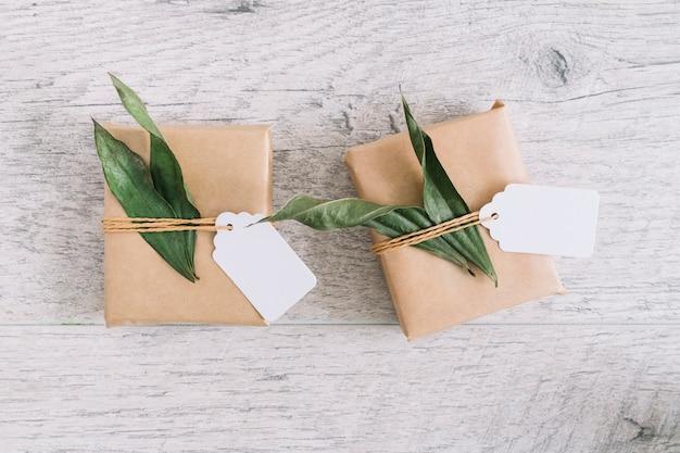 Marrón envuelto cajas de regalo con etiqueta en mesa de madera
