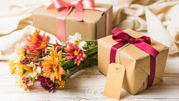 Marrón envuelto regalo con etiqueta vacía y hermoso ramo de flores