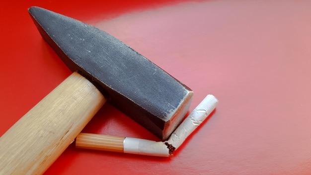 Martillo y un cigarrillo roto sobre un fondo rojo.