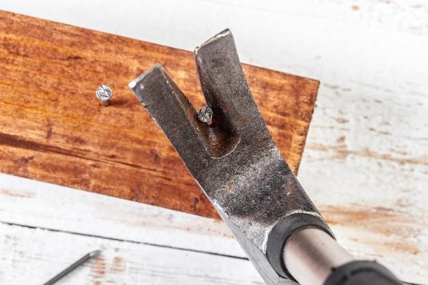Martillo y clavos sobre fondo de madera.