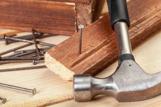 Martillo y clavos sobre madera.