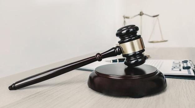 Martillo, escala de justicia y contrato sobre la mesa de madera.