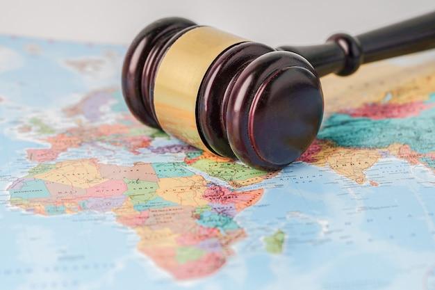 Martillo para juez abogado en el mapa del mundo mundial.