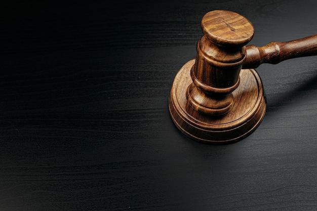 Martillo del juez en la mesa de madera en la oscuridad