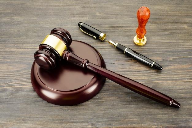 Martillo del juez, pluma estilográfica y un sello en una mesa de madera vieja