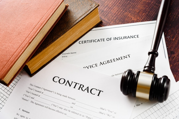 Martillo en los libros de leyes que regulan los contratos en papel para hacer negocios.
