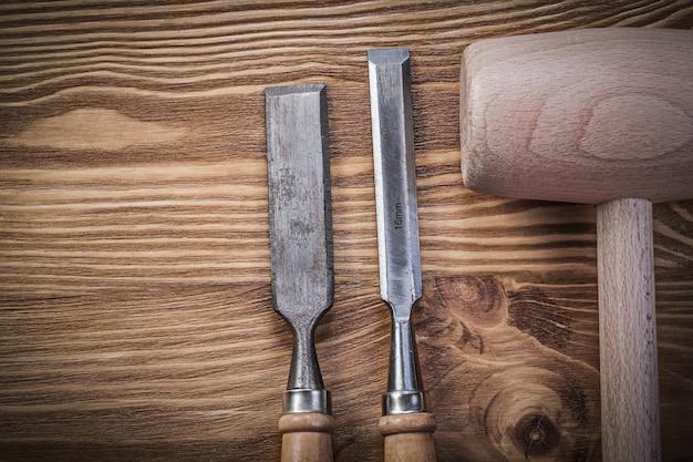 Martillo de madera cinceles más firmes sobre tablero de madera vintage