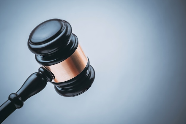 Martillo de madera de juez negro con fondo azul