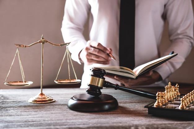 Martillo en mesa de madera y abogado o juez trabajando con acuerdo.