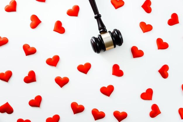 Martillo rodeado de corazones rojos aislados en blanco, amor por la justicia y el juez de la ley médica cumplimiento de la farmacia normas de negocios de atención médica.