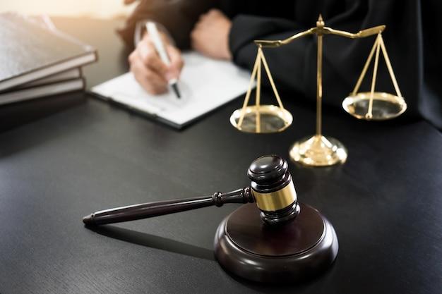 Martillo y soundblock de la ley de justicia y abogado que trabaja en fondo del escritorio de madera.