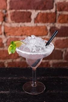 Martini cocktail con hielo y limón en una pared de ladrillos en un bar.