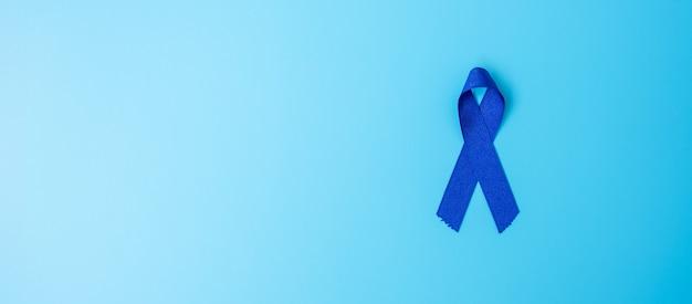 Marzo mes de concientización sobre el cáncer colorrectal, cinta de color azul oscuro para apoyar a las personas que viven y padecen enfermedades. concepto de salud, esperanza y día mundial contra el cáncer