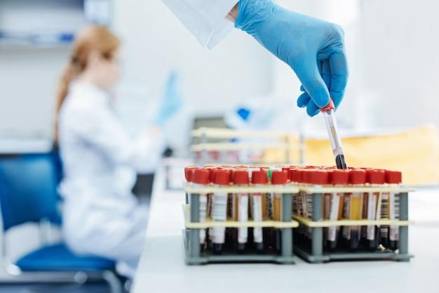 Más detalles. soporte de plástico de pie sobre la mesa mientras se llena con tubos de análisis de sangre