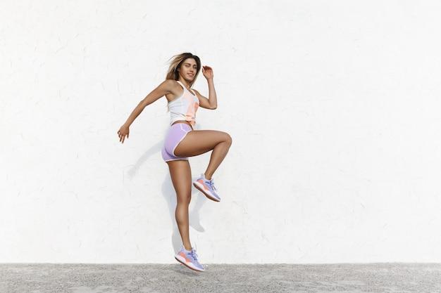 Más rápido, más fuerte, más alto. atractiva mujer de fitness atlético vistiendo ropa deportiva sonriendo durante el entrenamiento matutino