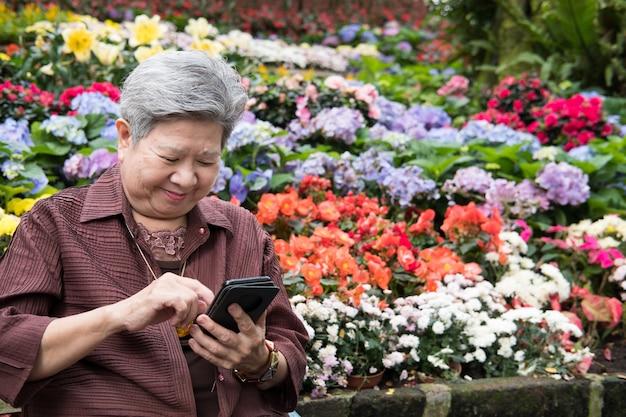 Una más vieja mujer que sostiene el teléfono móvil en jardín.