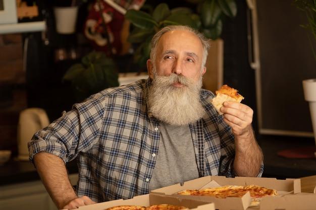 Más viejo hombre sonriente comiendo pizza rebanada sentado en la sala de estar. hombre barbudo senior comiendo comida italiana.