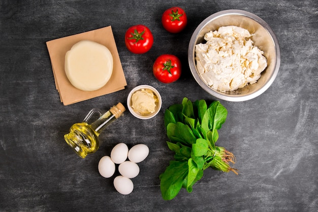 Masa, aceite, queso, tomates, huevos, verduras sobre superficie de madera gris.