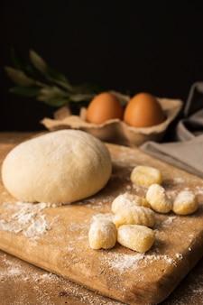 Masa de alto ángulo y ñoquis de patata en tabla de cortar