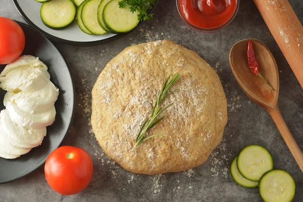 Masa cruda e ingredientes frescos para pizza vegana.