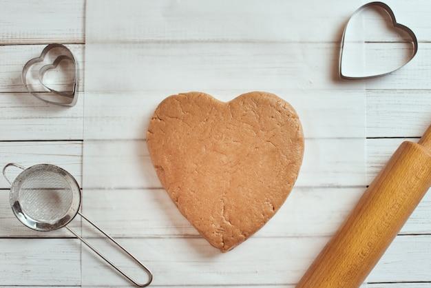 Masa cruda en forma de corazón sobre la mesa