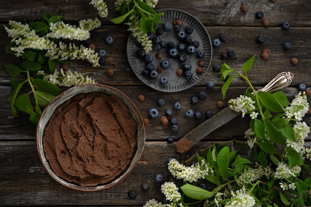 Masa cruda en un molde de pastel de cobre. bayas de arándanos y flores de cerezo.